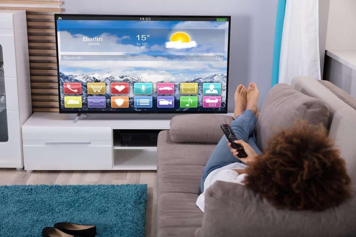 Frau schaut fernsehen auf Smart-TV