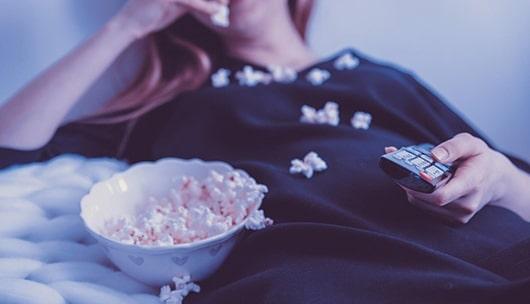 Frau beim Popcorn essen vor dem Fernseher